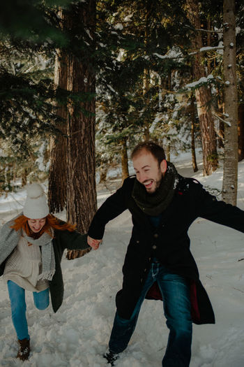 Full length of couple walking on snow covered landscape