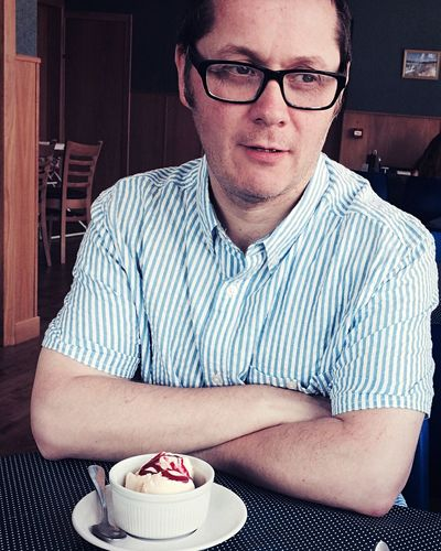 Man with ice cream on table at restaurant