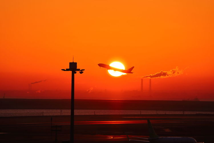 Sunset Sky Silhouette Orange Color Sun No People Transportation Nature Airport Beauty In Nature Airplane Air Vehicle Mode Of Transportation Street Street Light Flying Airport Runway Scenics - Nature Outdoors Bird Aerospace Industry