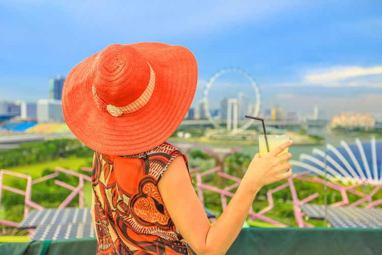 Travel holiday vacation in Singapore, Southeast Asia. Lifestyle caucasian woman with wide hat drinking aperitif at rooftop. Aerial view or cityscape skyline. Happy tourist enjoying at marina bay. Singapore Singapore City Woman Tourist Tourist Attraction  Tourist Destination People Girl Females Aerial View Skyline Cityscape Panorama Happy Travel Hat Lifestyle Enjoy Nature Tourism Smiling Aperitif Drink Orange Juice  Analcolic Glass One Person Sky Clothing Day Real People Leisure Activity Women Focus On Foreground Lifestyles Holding Adult Cloud - Sky Sunlight Outdoors Human Body Part Portrait Rear View