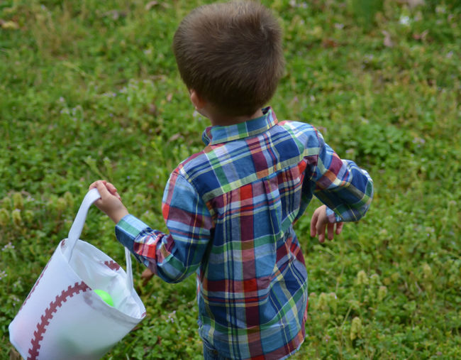 High angle view of boy holding white bucket on grassy field