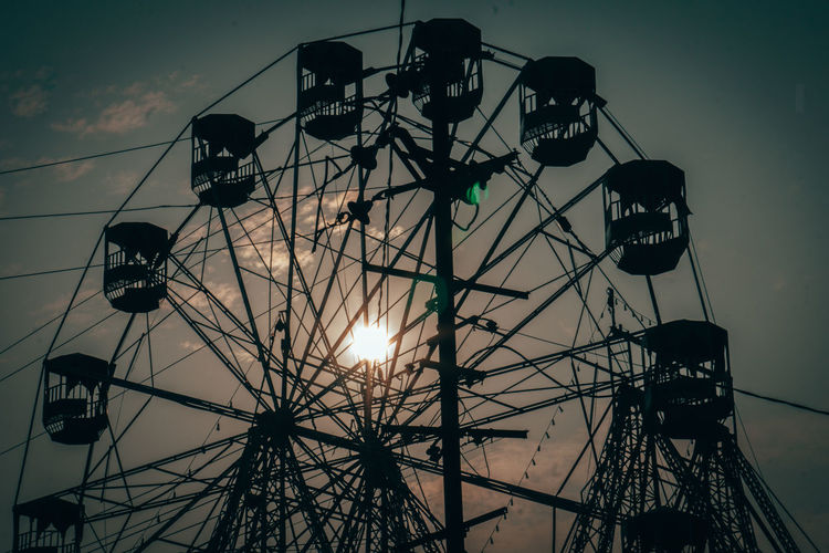 Low angle view of silhouette ferris wheel against sky at sunset