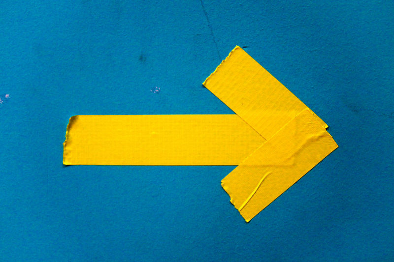 Close-up of yellow arrow symbol on paper