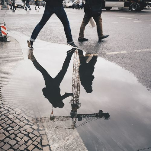 Reflection of men in puddle on street