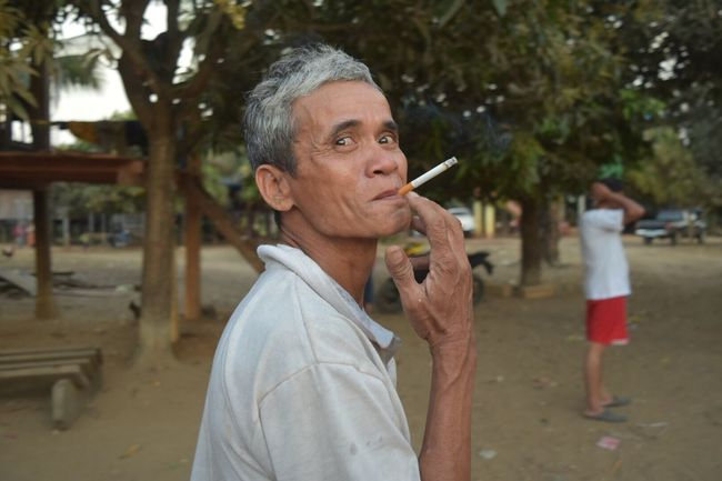 EyeEm Selects Casual Clothing Mature Adult Mature Men Focus On Foreground One Person Real People Bad Habit Men Looking At Camera Lifestyles Gray Hair Outdoors Day Close-up Adult People Smoking Portrait Cambodian Village Cambodia Village Old Man