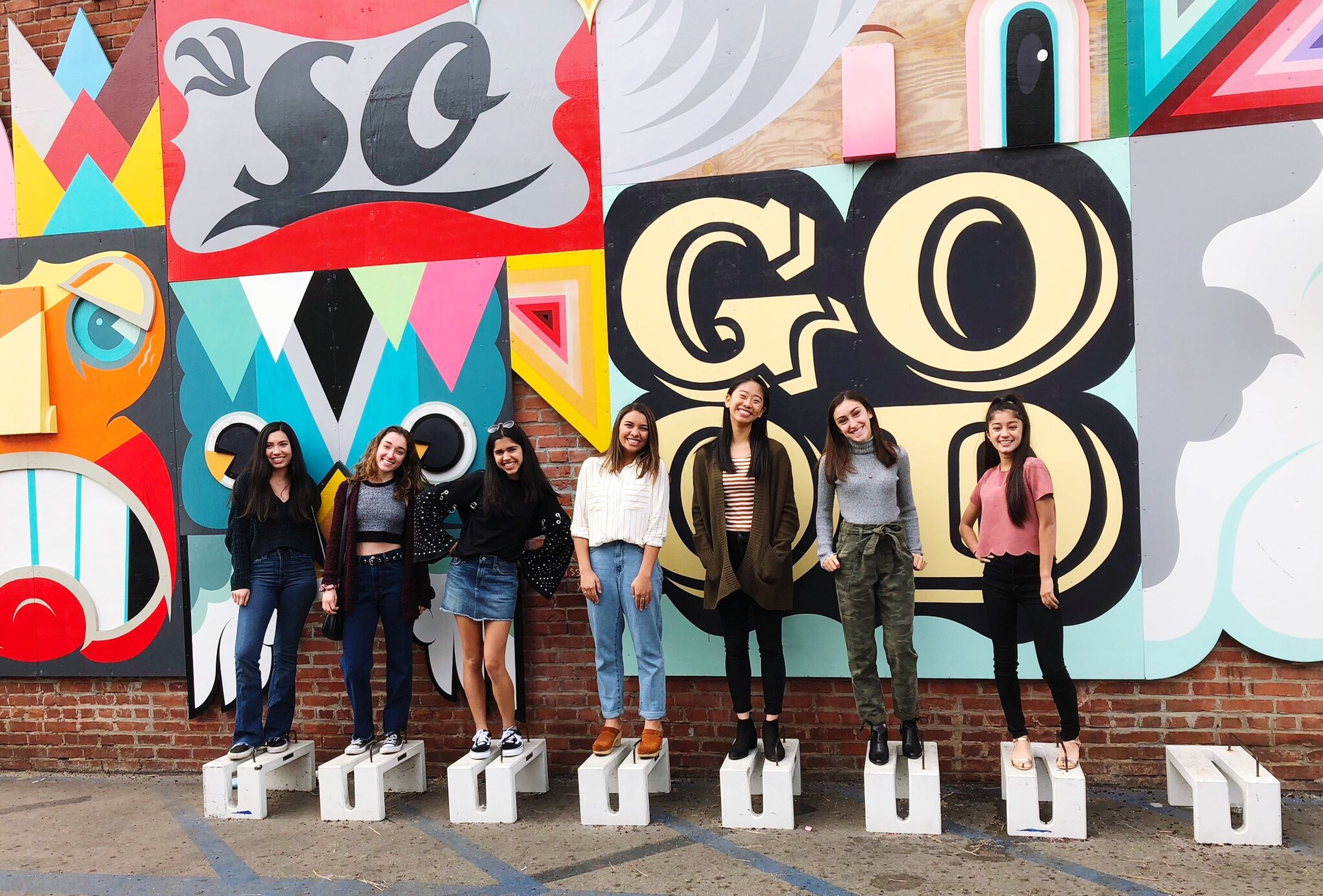 real people, standing, full length, casual clothing, graffiti, day, multi colored, lifestyles, leisure activity, outdoors, friendship, young women, young adult, one person, built structure, architecture, people