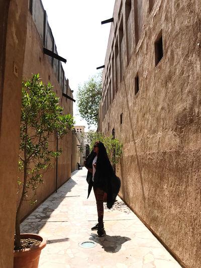 Full length of woman walking on footpath amidst buildings