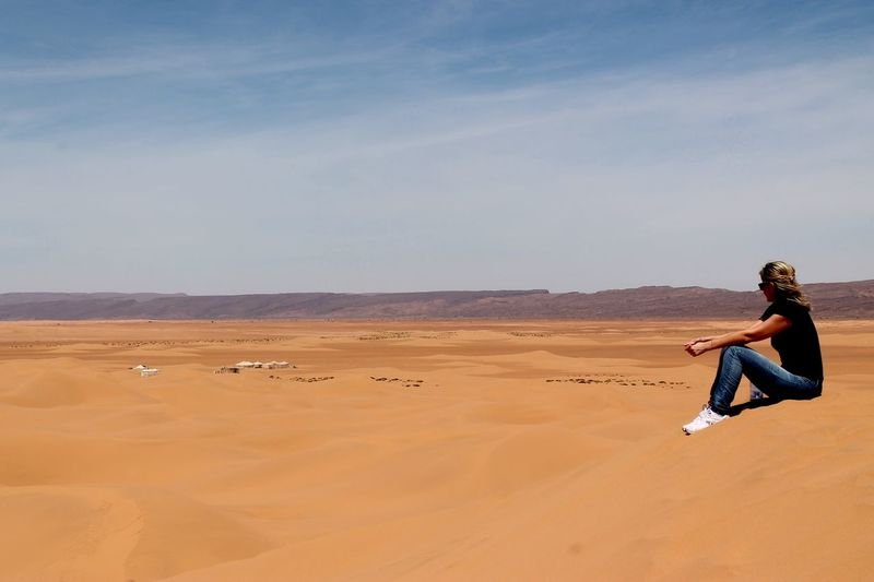 Side view of woman sitting on sand dune at sahara desert against sky