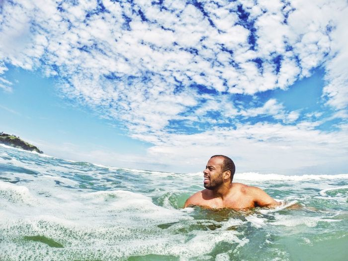 Man looking away while swimming in sea against sky