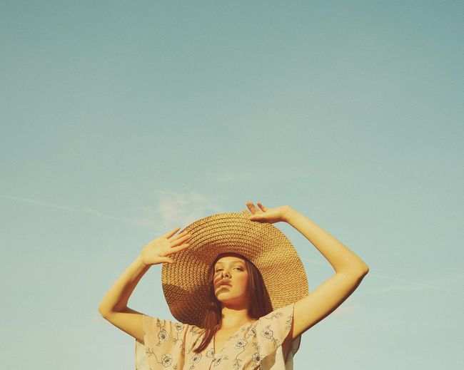 Portrait of young woman wearing hat standing against sky