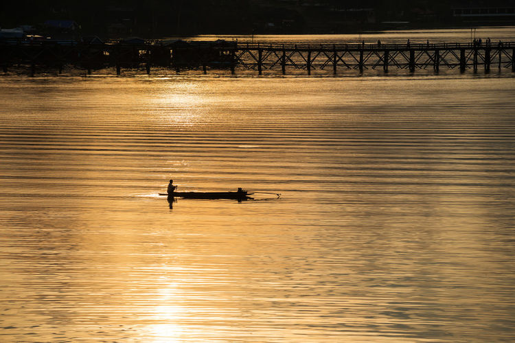 High angle view of silhouette person on boat in river during sunset