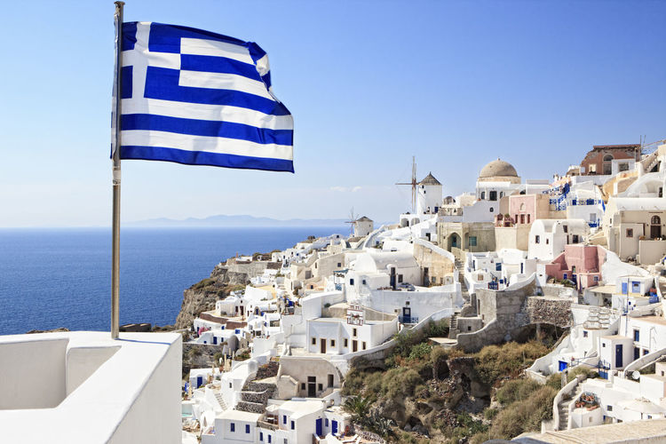 Close-up of greek flag by sea against clear sky