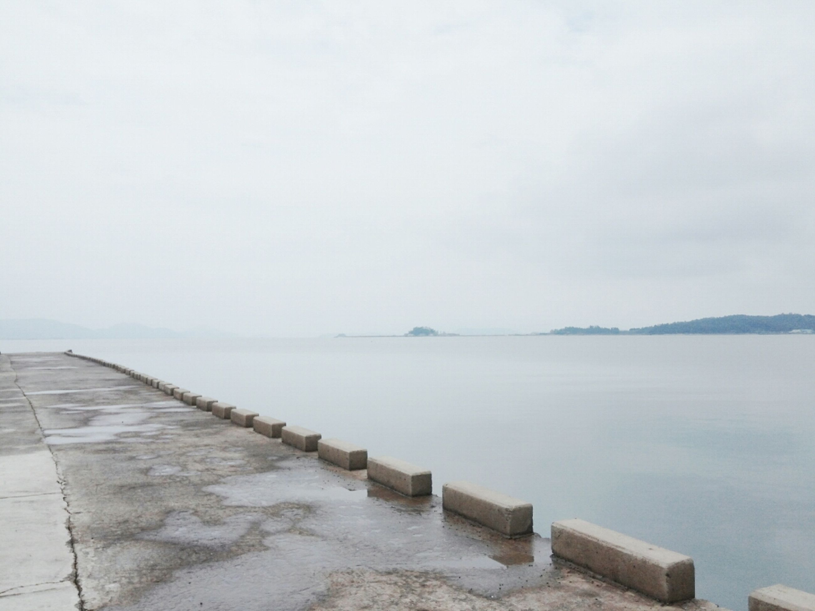 water, sea, tranquility, tranquil scene, sky, scenics, nature, copy space, pier, lake, beauty in nature, day, built structure, outdoors, calm, no people, idyllic, overcast, weather, horizon over water