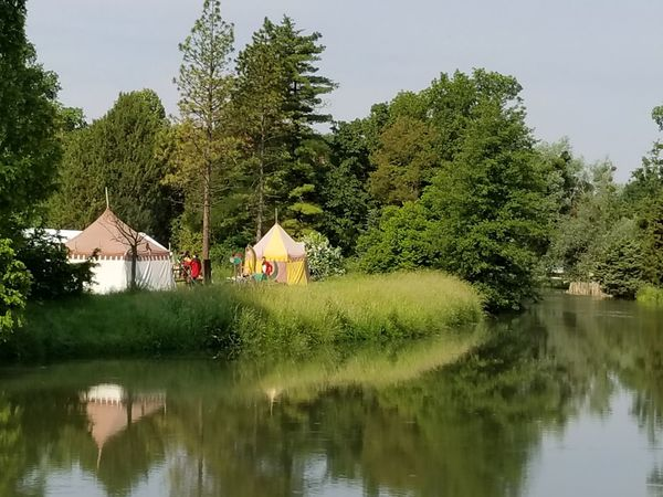 Medieval style tents on the bank of the Thaya River at Lednice Castle. Czech It Out Europe Display Field Nature Outdoors UNESCO World Heritage Site Grass River Riverside Trees Forest Tent Medieval Camp Water Reflection Sky Building Exterior Built Structure Tranquil Scene Countryside