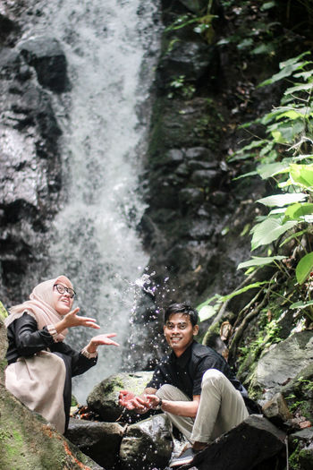 Couple sitting on rocks against waterfall
