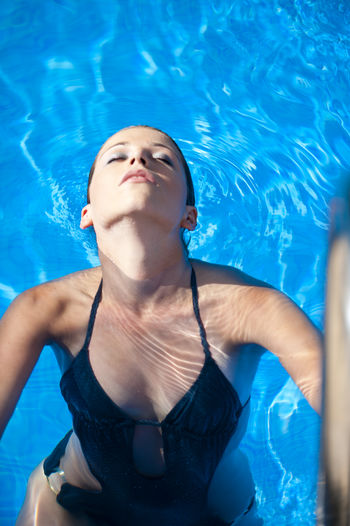 Portrait of sensuous woman standing in swimming pool