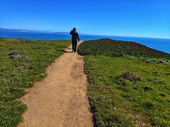 Man in Black on Ocean's Path. Man Solitude Solitary Alone Black Walking Hiking Sandstone Golden Blue Intense Headlands Dramatic Overlook Zen Soil Dirt Peaceful Therapeutic Background Ocean Distance Water Sea Full Length Shadow Sky Horizon Over Water Grass Hiker