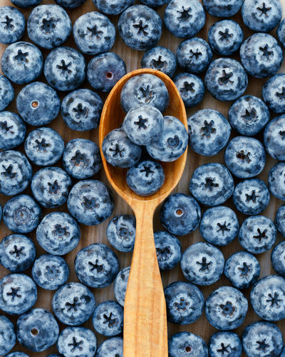 Fresh blue berries in a wooden spoon