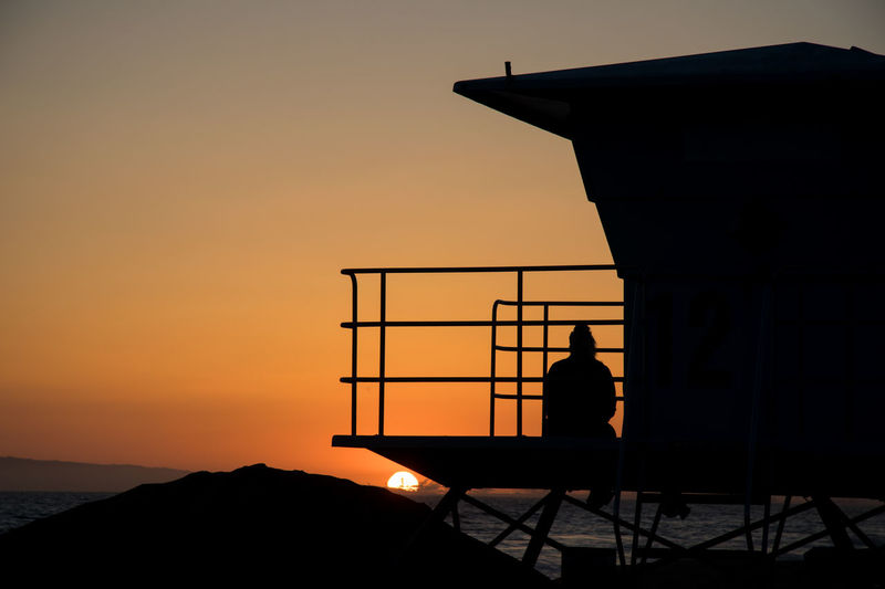 Silhouette person sitting on lifeguard hut at sea against sky during sunset