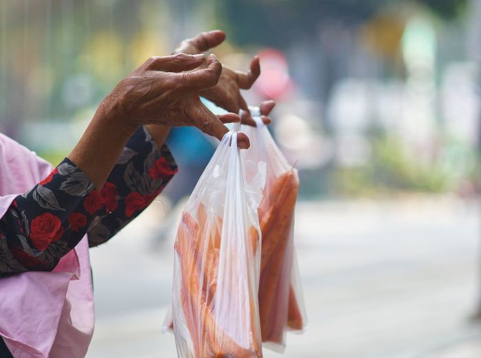 Cropped Hands Of Woman Holding Vegetables In Plastic Bags