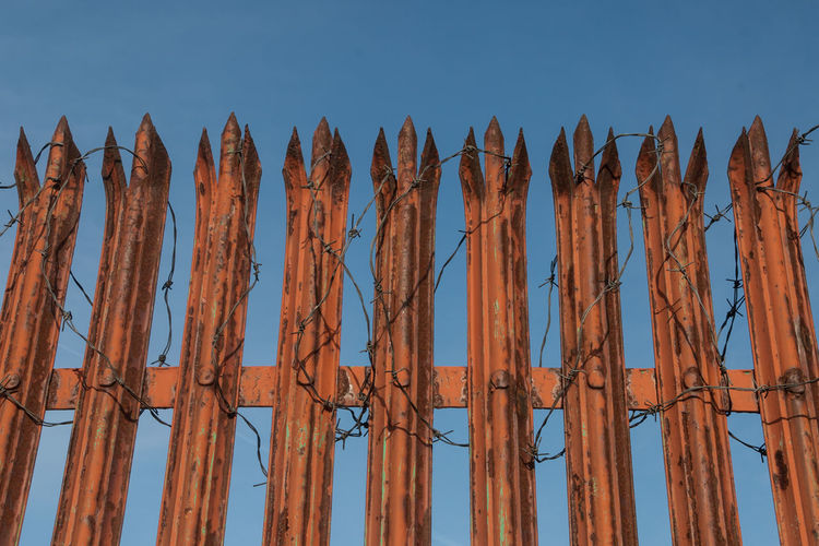 Low angle view of rusty fence with barbed wire