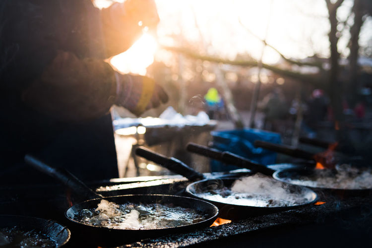Midsection Of Person Preparing Food During Sunset