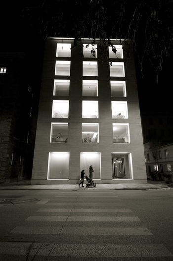 People walking on road amidst buildings at night