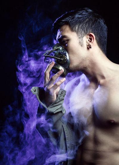 Shirtless Man Holding Mask By Smoke Against Black Background