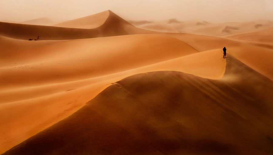 Person hiking on sand dunes in desert