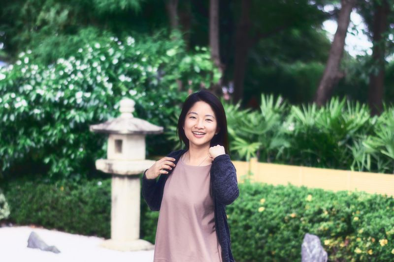 Asian girl relaxing in Japanese garden. Smiling Happiness Young Women Lifestyles Black Hair Cheerful Outdoors Tree Leisure Activity Standing Girl Portrait Relaxing Leisure Activities Freshness Asian