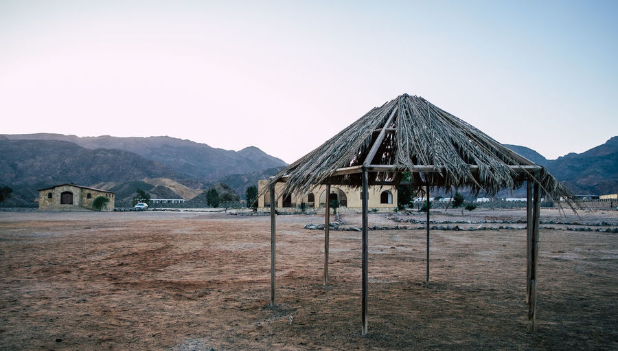 Built structure on field by mountains against clear sky
