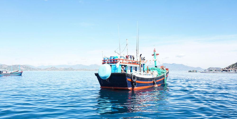 Trawler in sea against sky