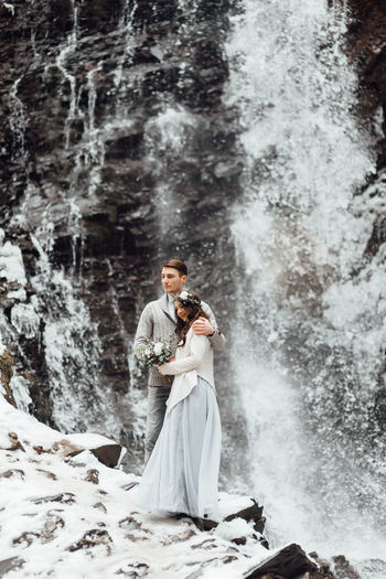 Full length of young man standing in waterfall