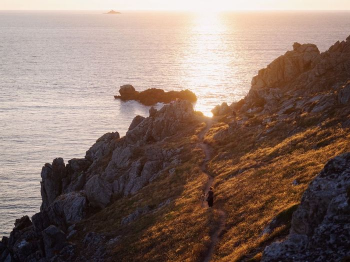 High Angle View Of Woman Walking With Dog On Cliff Against Sky During Sunset
