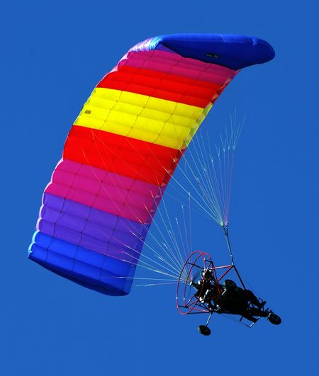 A very colorful ultralight flying in a very blue sky with a rainbow parachute. Adventure Blue Clear Sky Day Exhilaration Extreme Sports Flying Freedom Full Length Leisure Activity Lifestyles Low Angle View Mid-air Multi Colored Outdoors Parachute Paragliding Parasailing Real People RISK Sky Skydiving Sport Transportation Unrecognizable Person