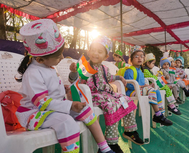 Cute kids wearing costume sitting on chair outdoors