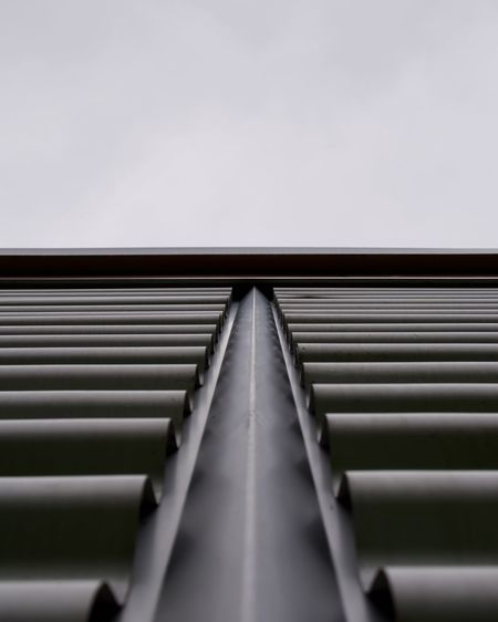 Low angle view of metal wall against sky