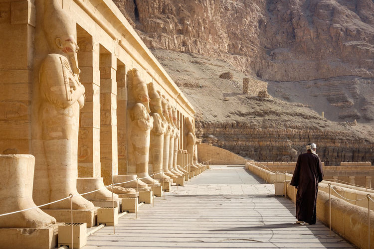 Guard walks along the second terrace of the mortuary temple of Hatshepsut at Deir el-Bahri, on the west bank of Luxor, in Egypt Africa Ancient Ancient Civilization Archaeology Architecture Built Structure Colonnade Day Deir El Bahri Desert Egypt Hatshepsut History Luxor Morning North Africa One Person Outdoors People Pharaoh Statues Temple Tourism Travel First Eyeem Photo