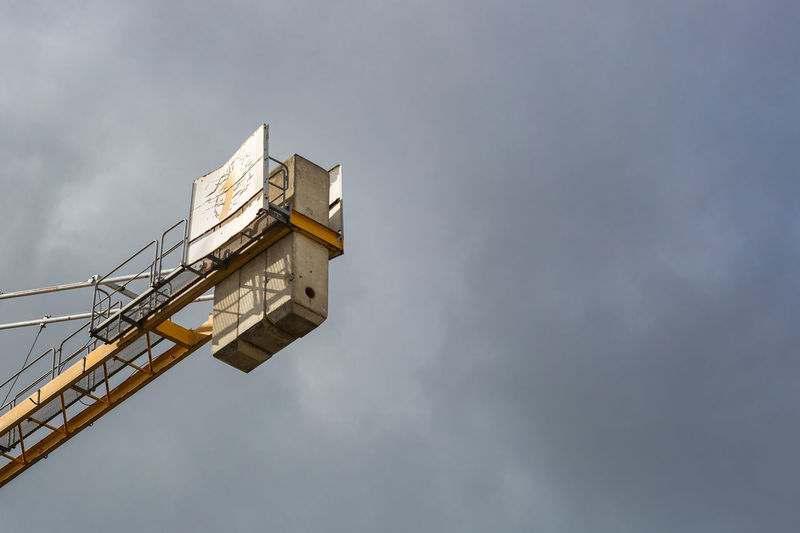 Low angle view of cherry picker against cloudy sky