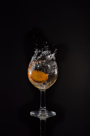 Close-up of water splashing in glass against black background