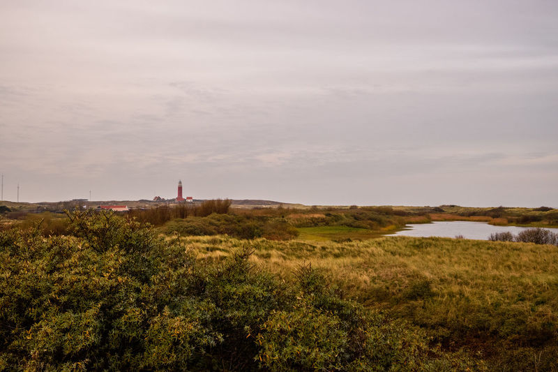 Scenic view of landscape and lighthouse against sky
