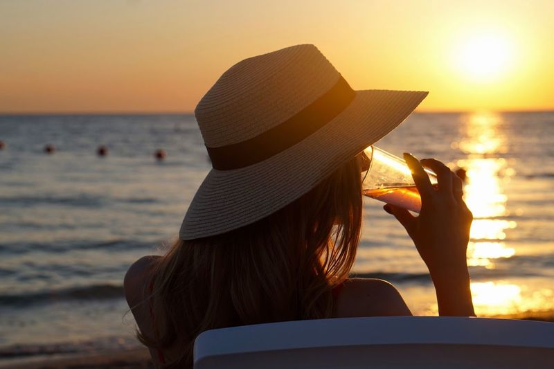 Young woman having drink at beach during sunset