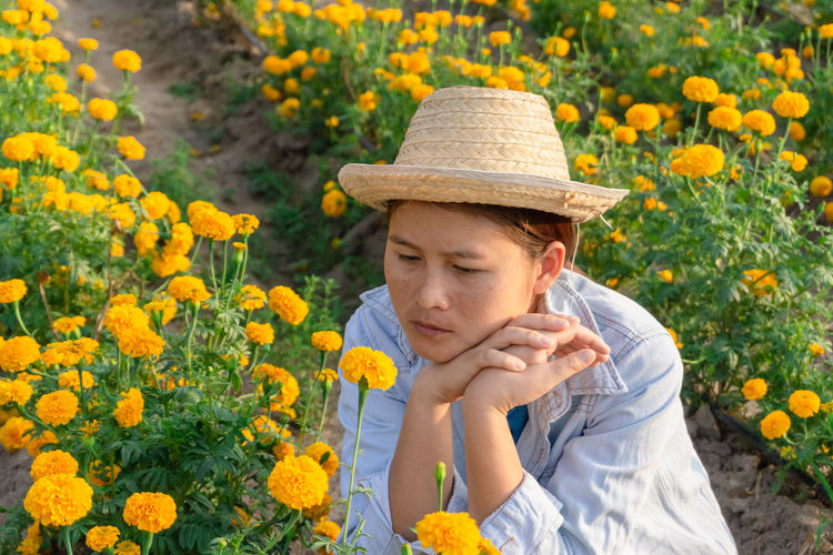 Marigold Portrait Flower Marigold Flower Farmer Selective Focus Lifestyles Outdoors Nature Plant Leisure Activity Care Check Flowering Plant One Person Hat Yellow Freshness Front View Growth Beauty In Nature Clothing Vulnerability  Fragility Day Real People Sun Hat Contemplation Flower Head