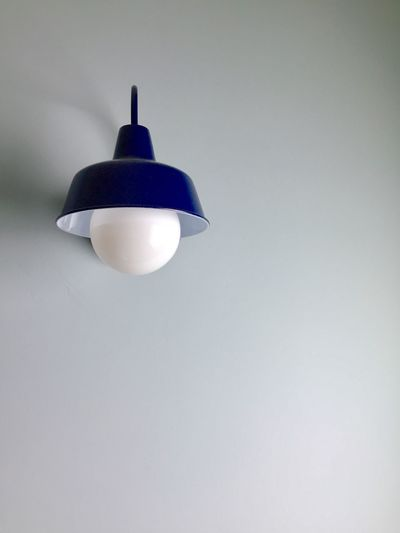 Low angle view of illuminated light bulb against wall