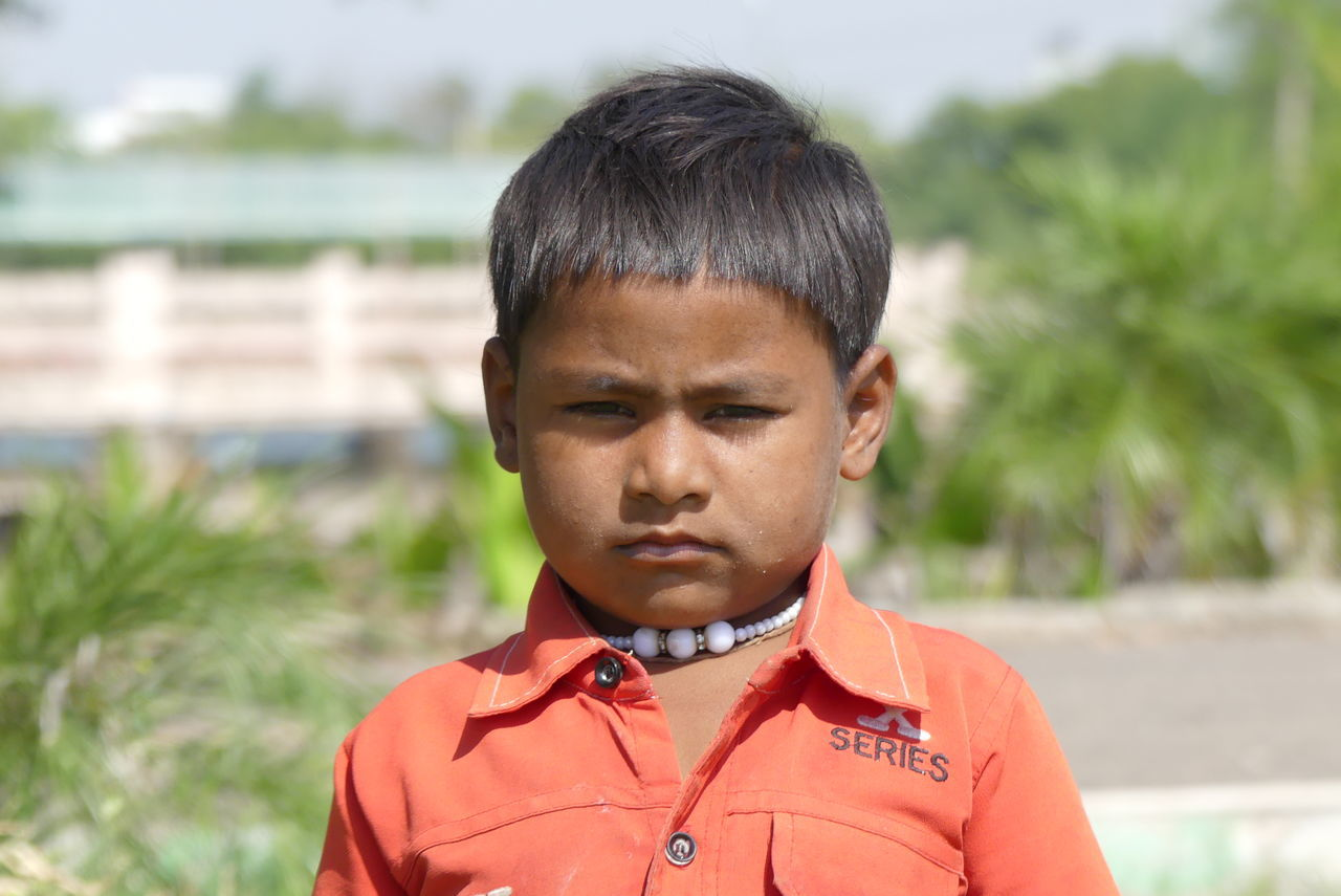 focus on foreground, headshot, real people, day, boys, one person, childhood, outdoors, front view, close-up, standing