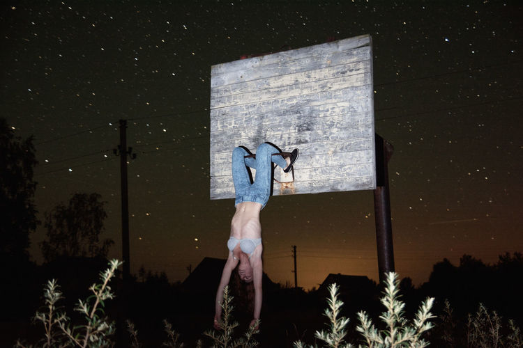 Young woman hanging on abandoned basketball hoop at night