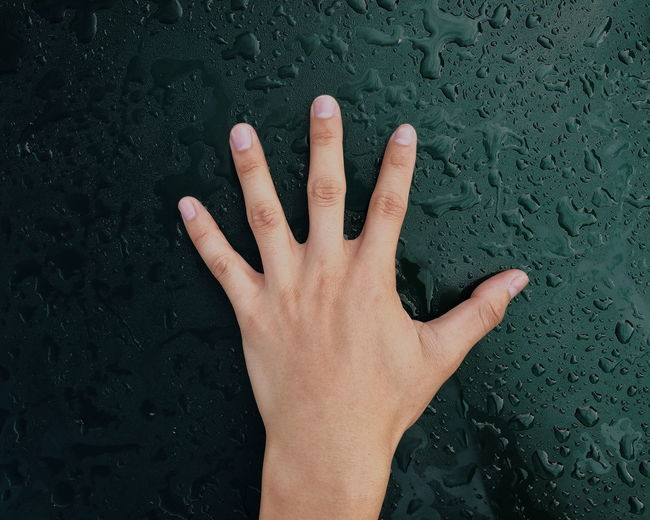 Cropped Hand Of Person Touching Wet Glass Window