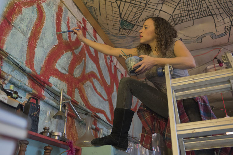 Low angle view of woman sitting on wall