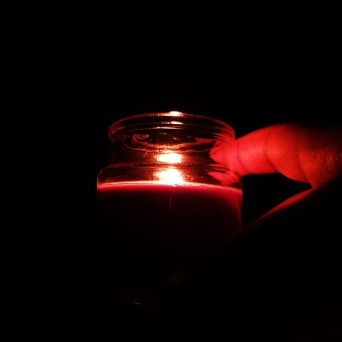 Close-up of hand holding illuminated candle against black background