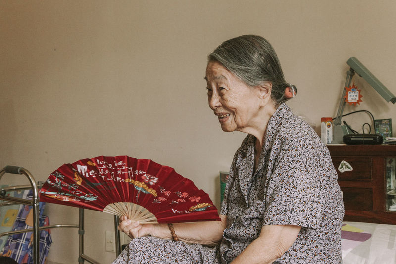 Side view of smiling senior woman holding hand fan while sitting at home